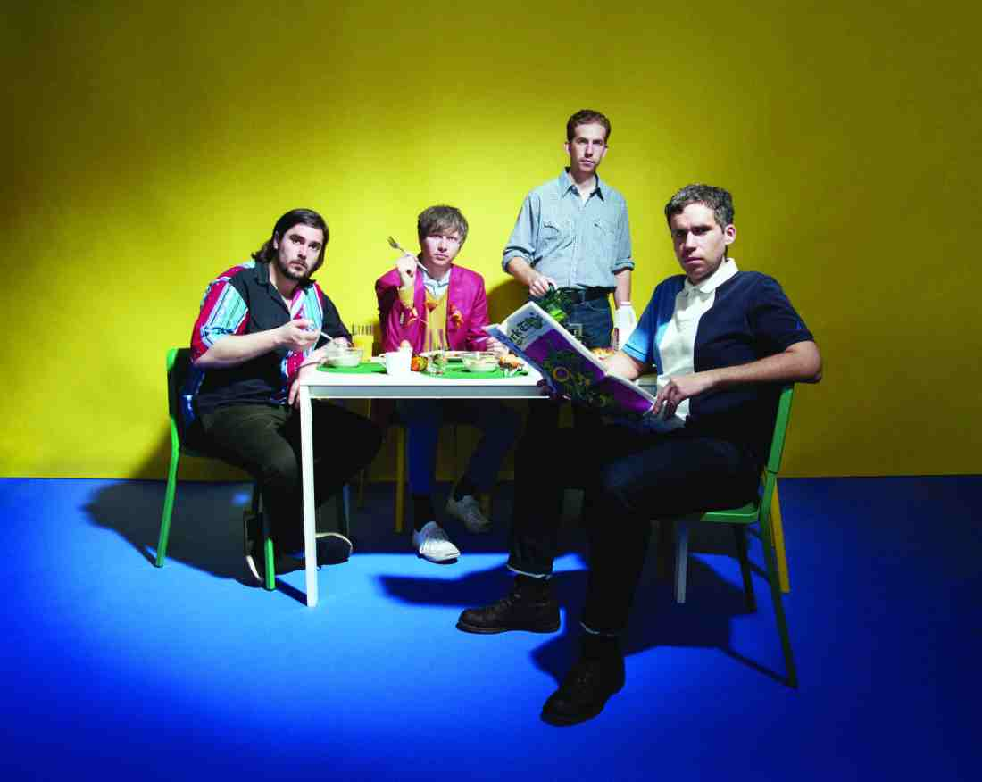 A photograph of Parquet Courts sat around a breakfast table, pouring coffee, reading a newspaper and eating cereal. The floor is a electric blue and the background wall is bright yellow.