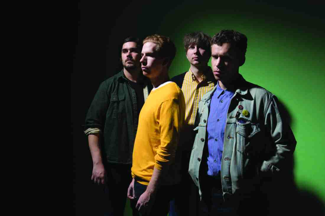 The band stand together, looking slightly left. The background is green and Parquet Courts are backlit, creating heavy shadow on their faces and blackening the green background completely on the left-hand side.