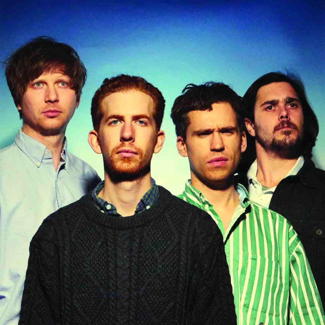 The band face the camera head on and look into the lens with blank or confused expressions. The background fades from a navy blue around the edges into a mint green at the centre of the image.