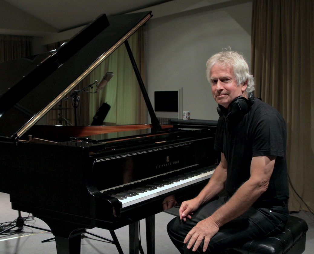 An image of Tony Banks of Genesis sitting at a grand piano. He wears all black with a pair of over-ear headphones resting around his neck and his lips are pressed in a small smile as he looks at the camera. The grand piano is black and the lid is propped open. There are microphone stands and other recording equipment in the background.